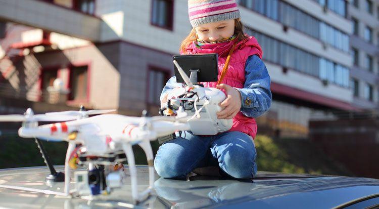 Niña de rodillas en el suelo viendo cómo volar un drone